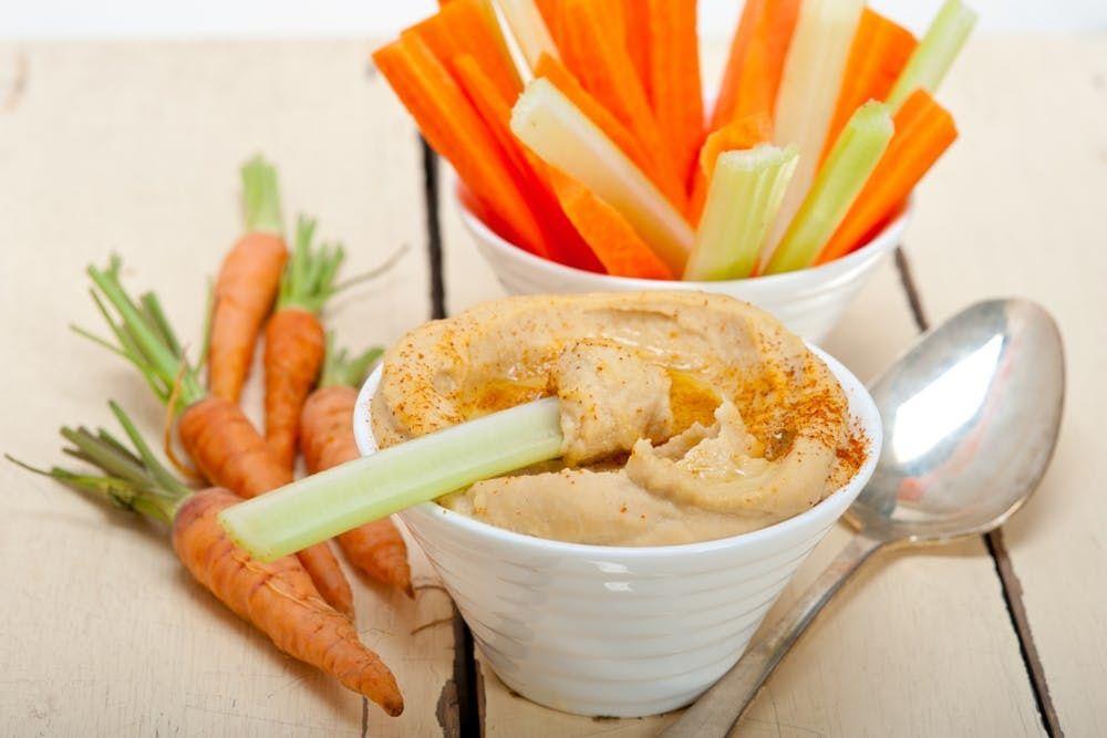 Frischer Hummus wird mit Sellerie und Karottensticks serviert