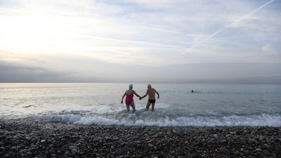An older couple holds hands going into the water.