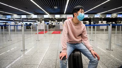 Man with mask sitting on suitcase in empty airport