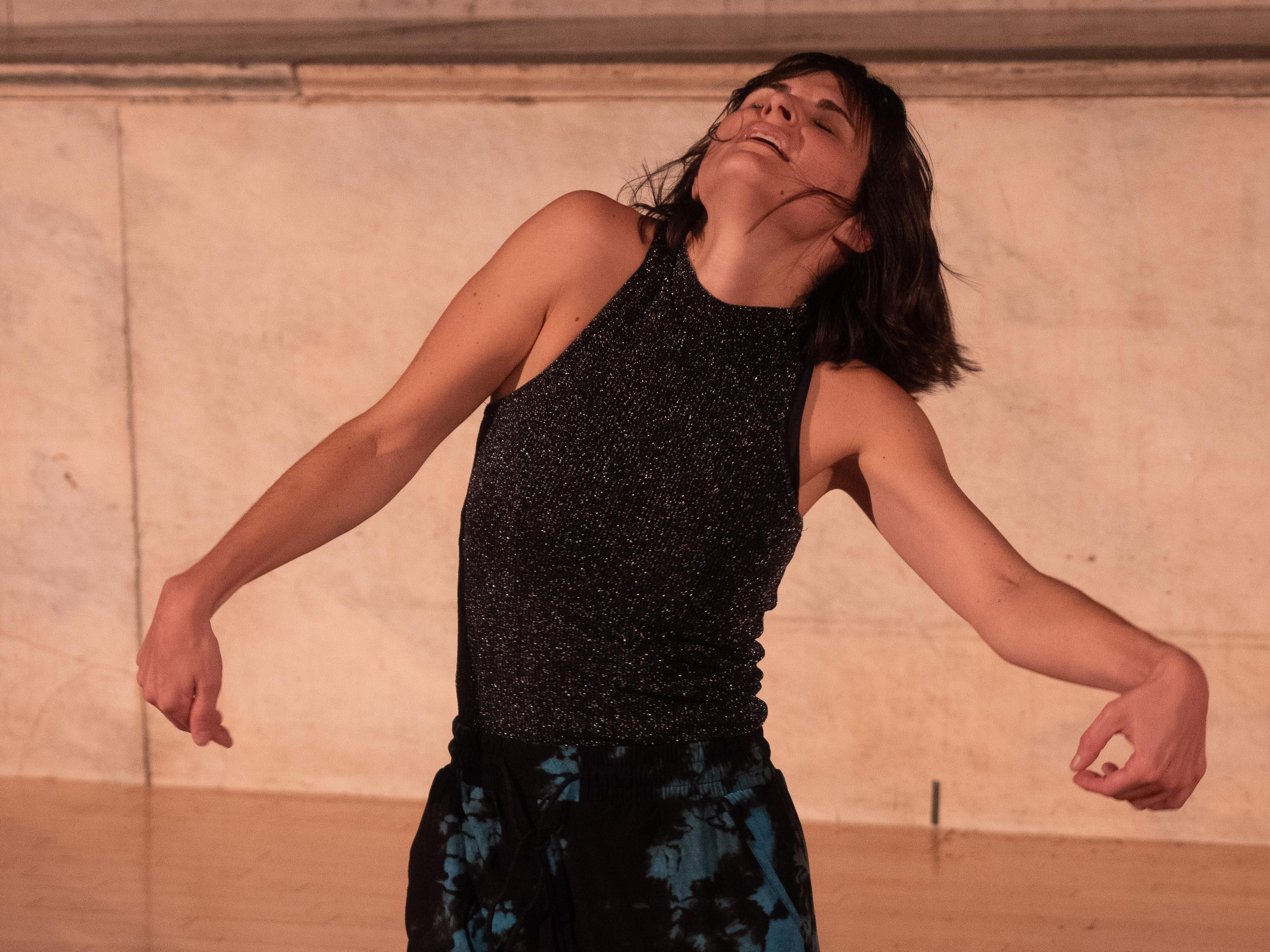 Elisabeth Motley, a white woman with chin-length layered brown hair with bangs, dances in front of a beige marble altar. She wears a form-fitting sleeveless black shirt woven with subtle glitter thread and blousy capri length pants that are tie-dyed teal and black. She faces the camera and her arms are jetting sideways from her body on opposing downward diagonals. Both hands are loosely clenched in inwardly rotated fists. Her right shoulder is higher than her left and her head is thrown backwards on the upstage right diagonal. Her eyes are closed, mouth slightly open, strands of hair cling to her face. The image cuts off at mid-thigh.