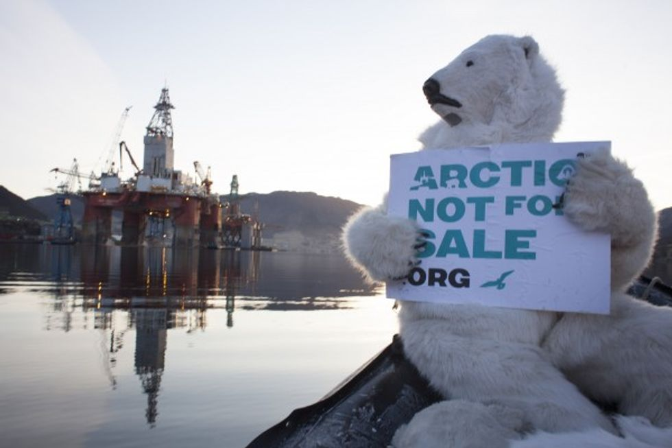Greenpeace activist holding sign outside of drilling rig