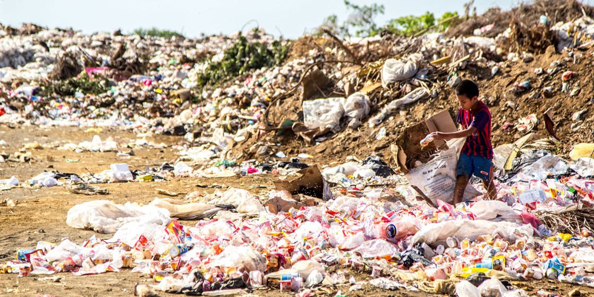 young boy searches plastic waste