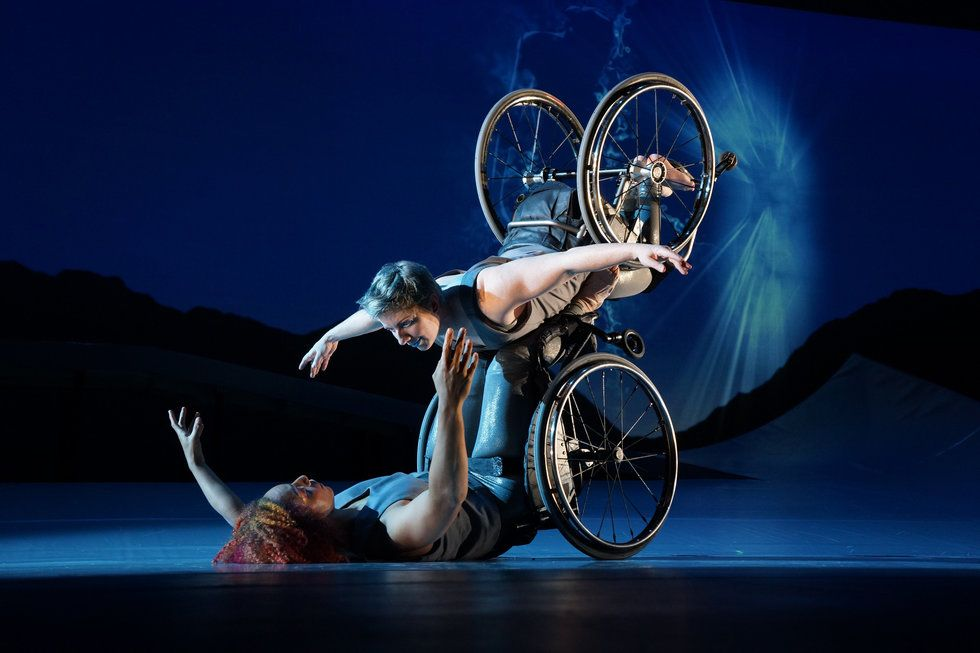 Laurel Lawson as Venus is flying in the air with arms spread wide, wheels spinning, and supported by Alice Sheppard as Andromeda who is lifting from the ground below. They are making eye contact and smiling. Photo by Jay Newman/BRITT Festival.