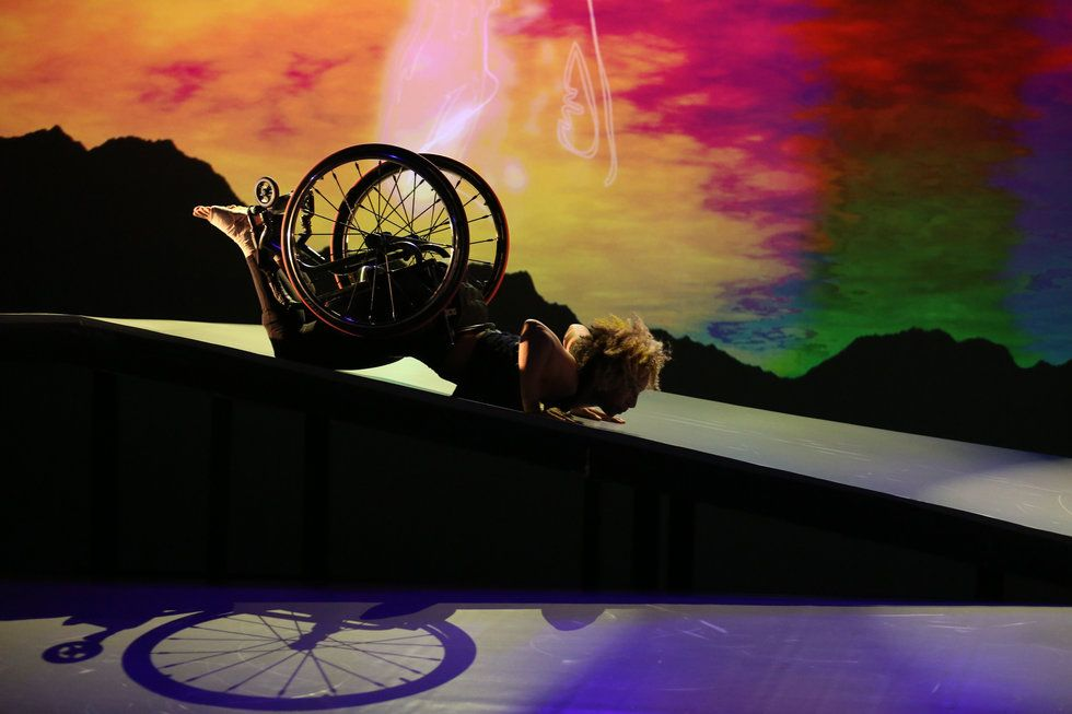 Alice Sheppard on the ramp for DESCENT. She is face down, supporting her weight with her hands. A shadow of her chair is illuminated by the stage lighting. Photo courtesy MANCC.