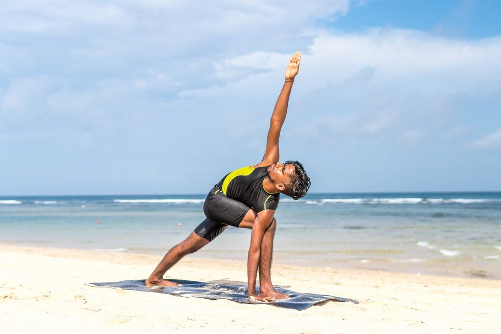 attractive fit young man doing yoga on the beach