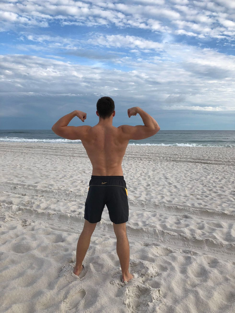 fit man flexing muscles on beach