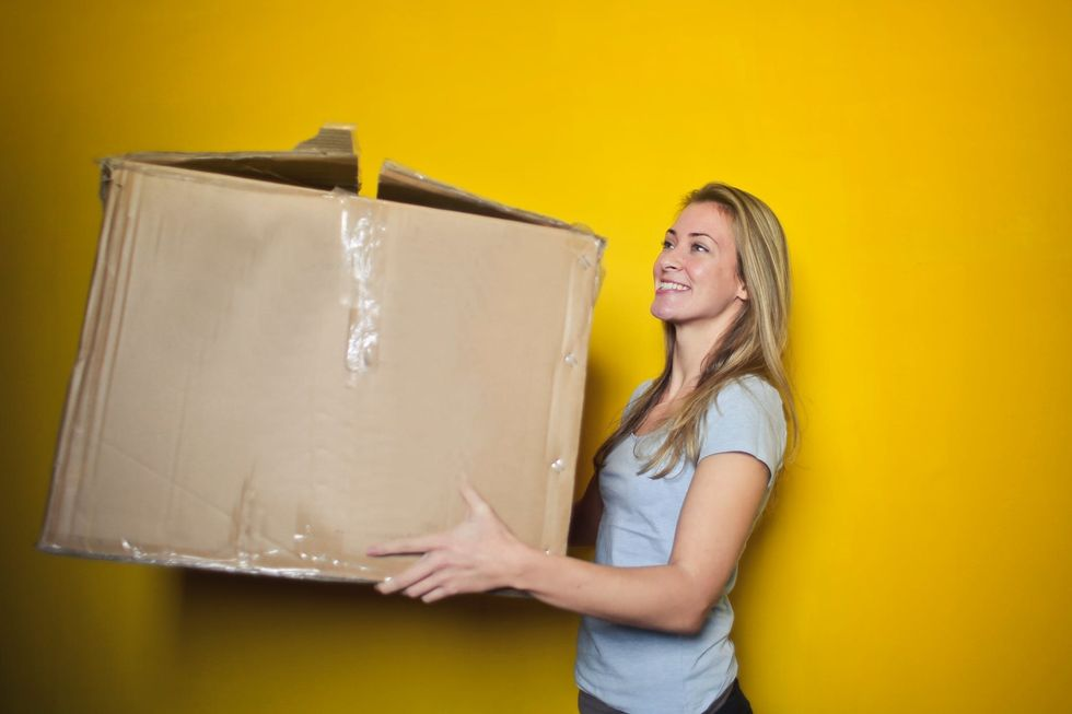 https://www.pexels.com/photo/woman-in-grey-shirt-holding-brown-cardboard-box-761999/