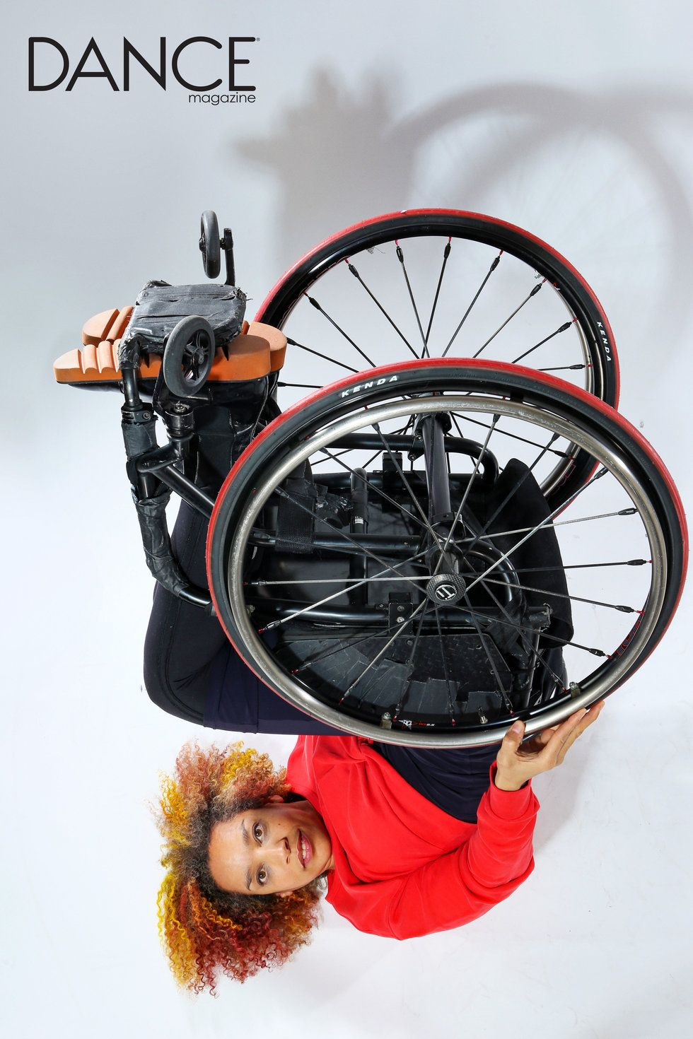 Alice Sheppard is upside down with wheels reaching to the sky. She looks directly at you. You can see the underside of her wheelchair, as though she is presenting it to you. Photo by Jayme Thornton.