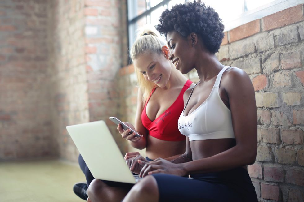 https://www.pexels.com/photo/two-women-wearing-red-and-white-sports-bras-sitting-near-brown-wall-bricks-863950/