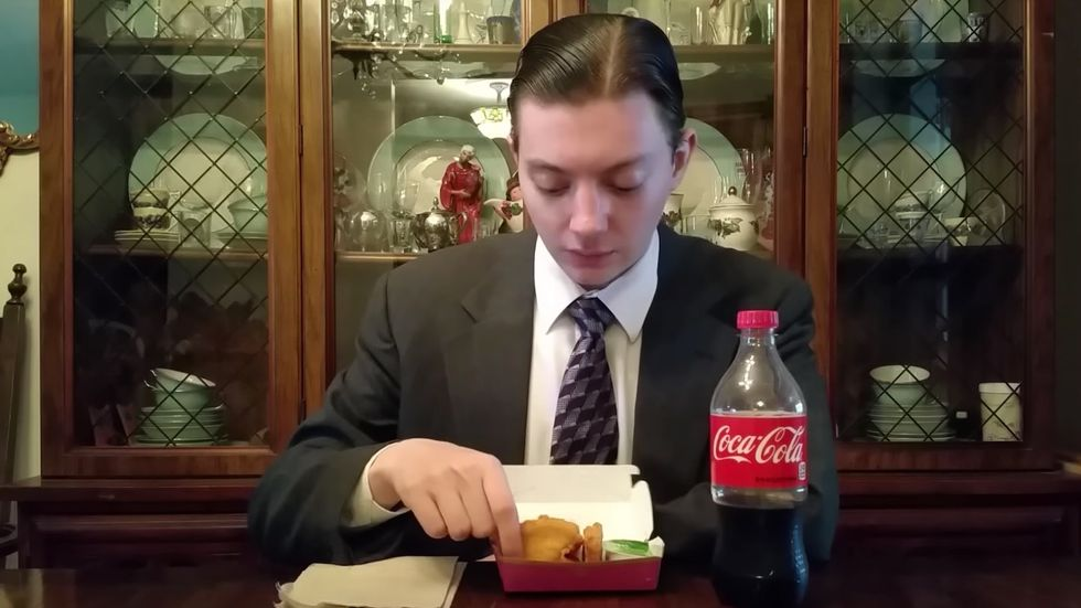 college student eating fast-food mcdonald's chicken nuggets and coke