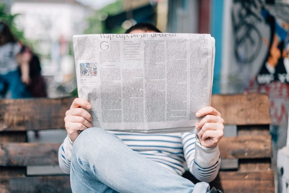 person sitting on bench reading newspaper