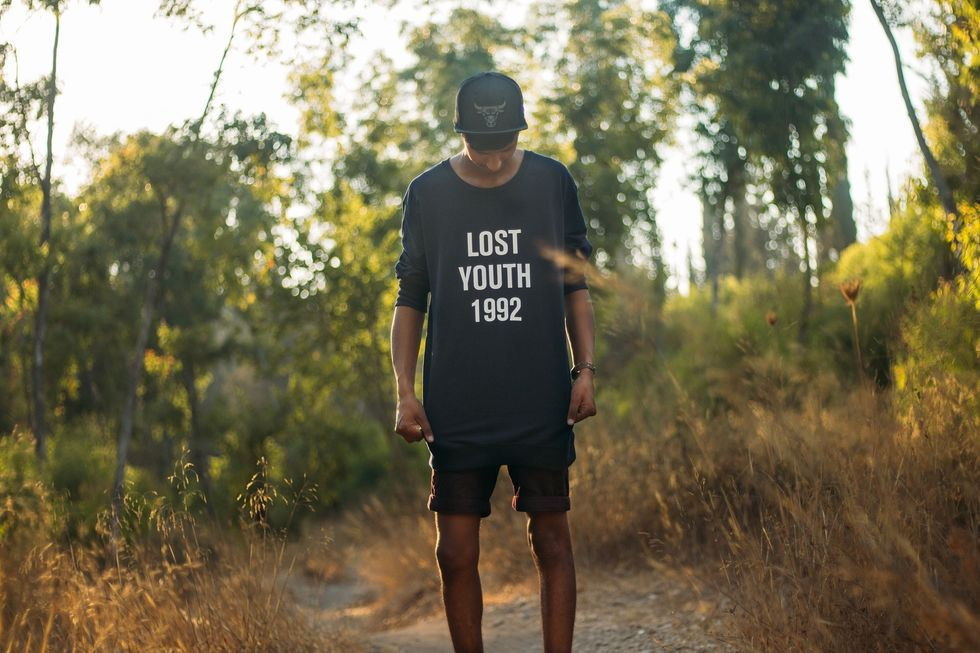 guy standing in the wild with a lost youth shirt