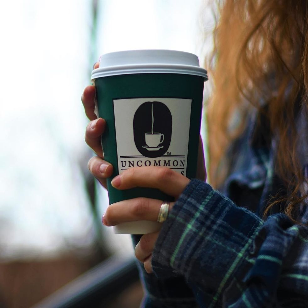 person holding cup of uncommon grounds coffee