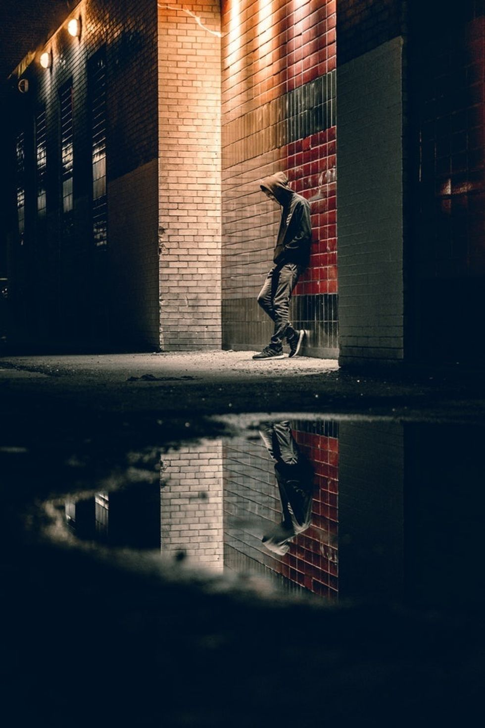 man in hood standing against brick wall in alleyway