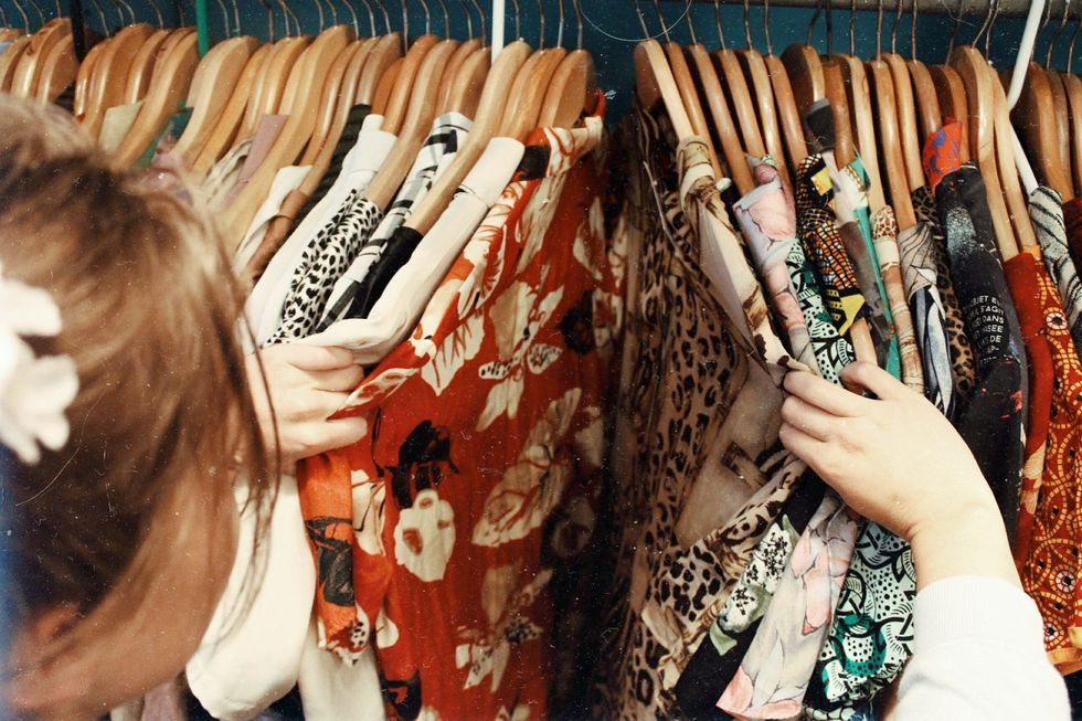 Woman sifting through racks of clothes