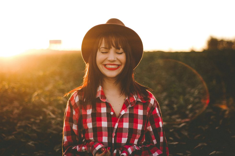 Girl wearing a plaid shirt and a hat smiling