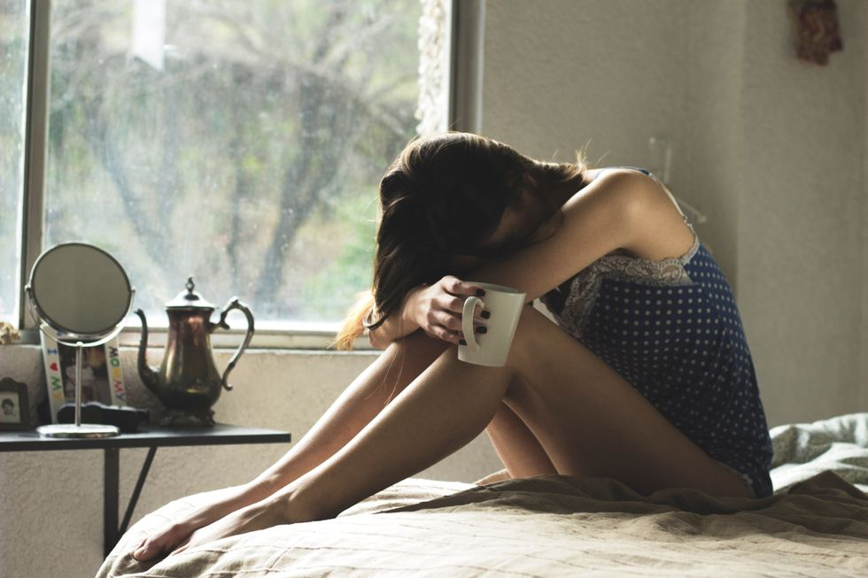 Girl sadly sitting on a bed with a mug in hand