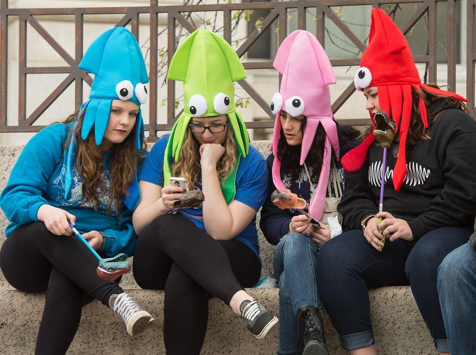 Teen girls wearing squid hats.
