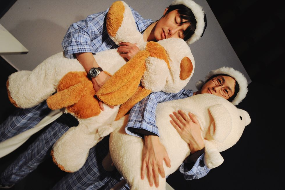Two Japanese men in sleep clothes with teddy bears.