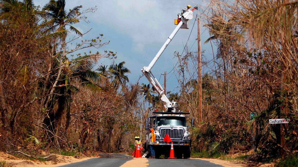 Puerto Rico Power Authority workers repair power lines in the aftermath of Hurricane Maria, in Loiza, Puerto Rico, September 28, 2017. The US island territory, working without electricity, is struggling to dig out and clean up. (RICARDO ARDUENGO/AFP/Getty