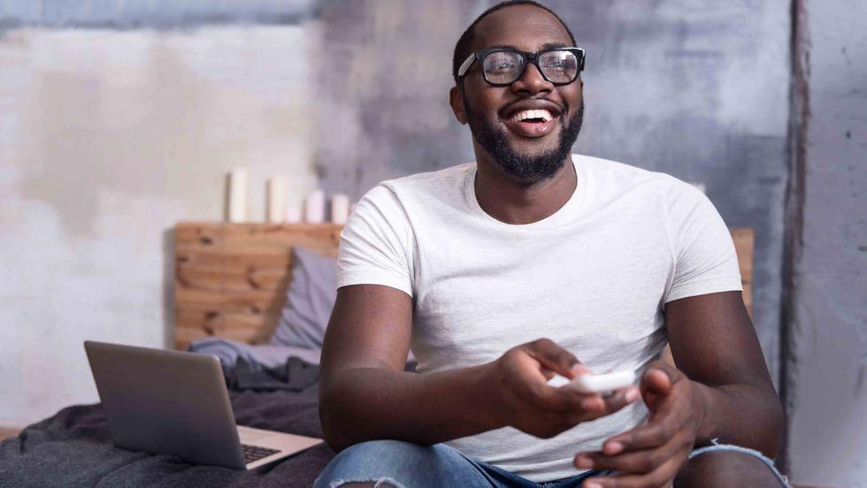 A young man watching TV. (Shutterstock)
