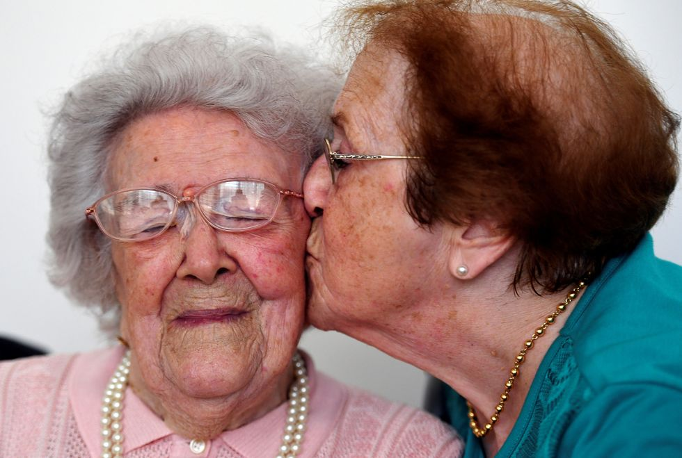 A senior being kissed by another old woman.