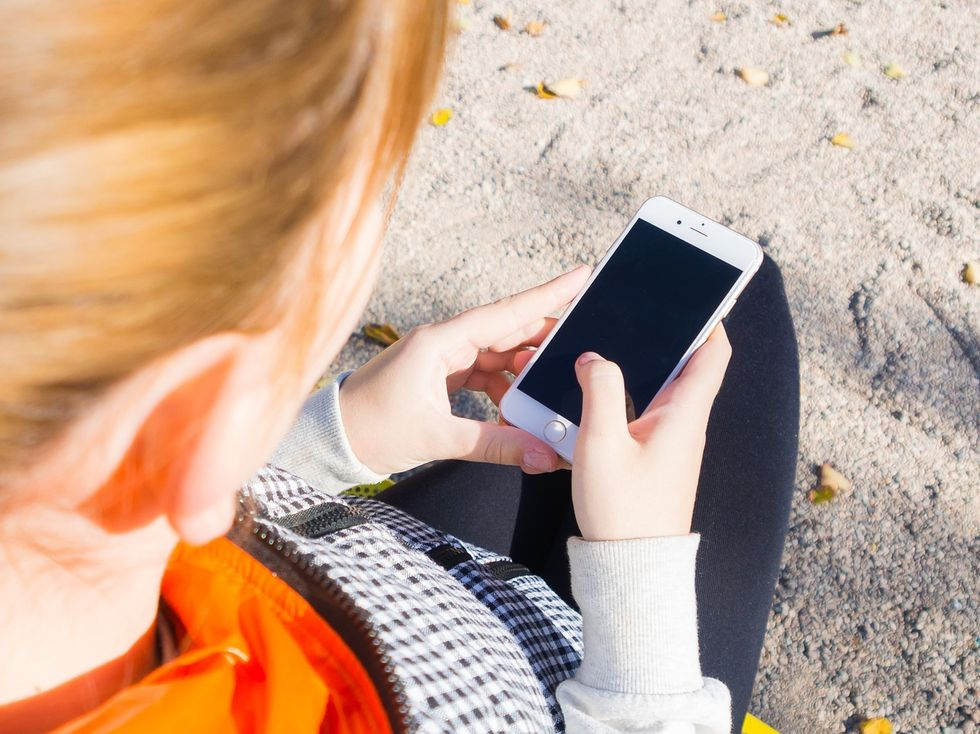 Girl looking at her smartphone on the beach.