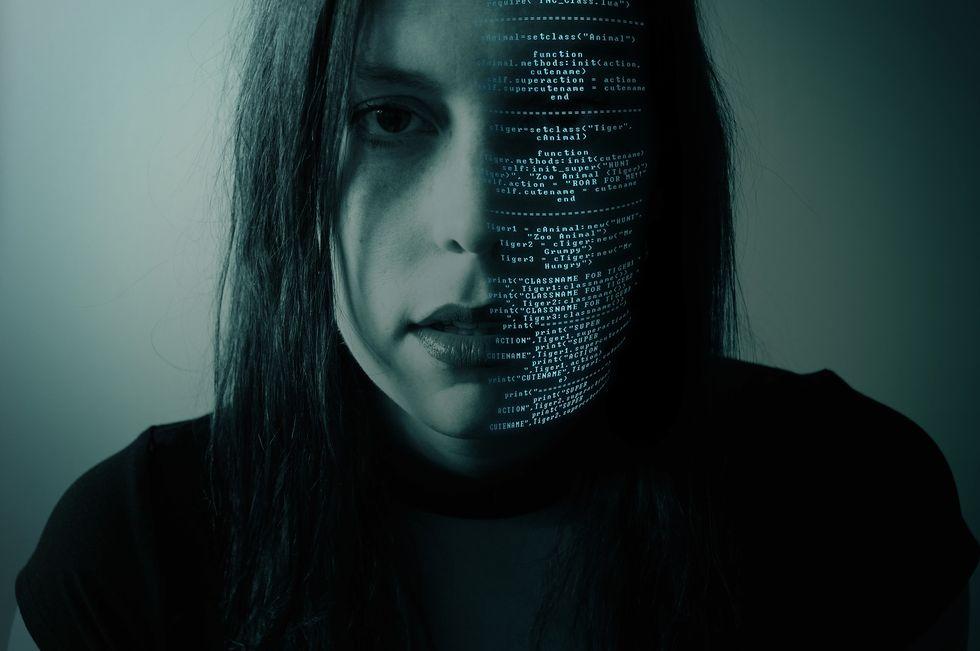 Girl's face, half in code.
