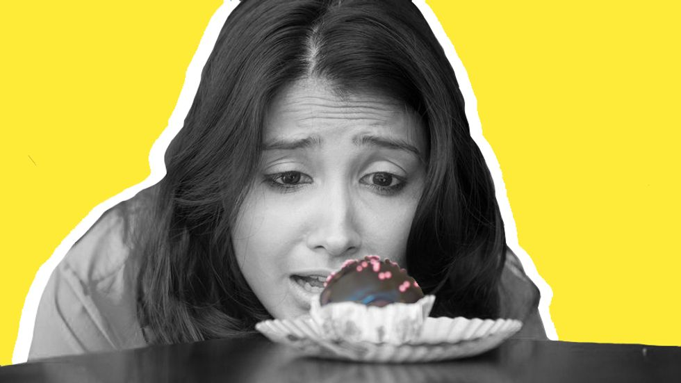 A woman with sugar cravings looking at cupcake. Photo: Shutterstock