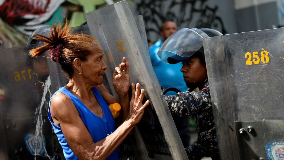 A woman confronts riot police during a protest in Caracas on December 28, 2017. Getty Images