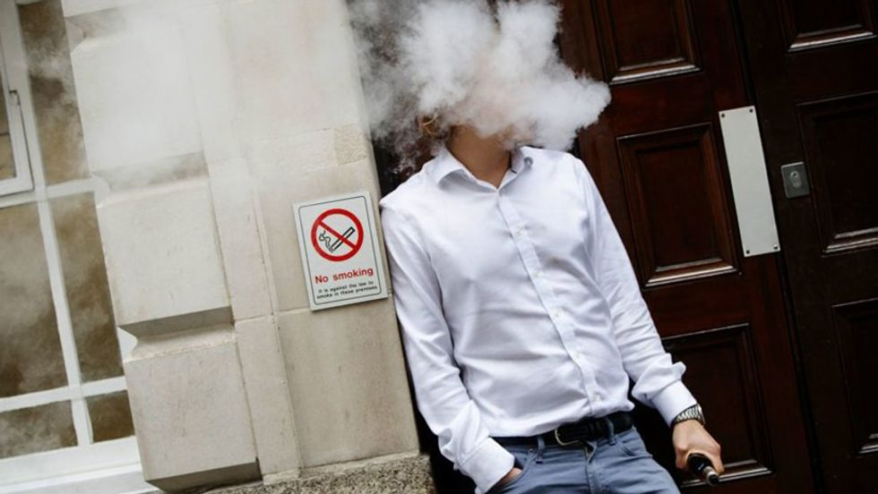 A smoker is engulfed by vapors as he smokes an electronic vaping machine during lunch time in central London on August 9, 2017. (Photo by Tolga Akmen/AFP/Getty Images)