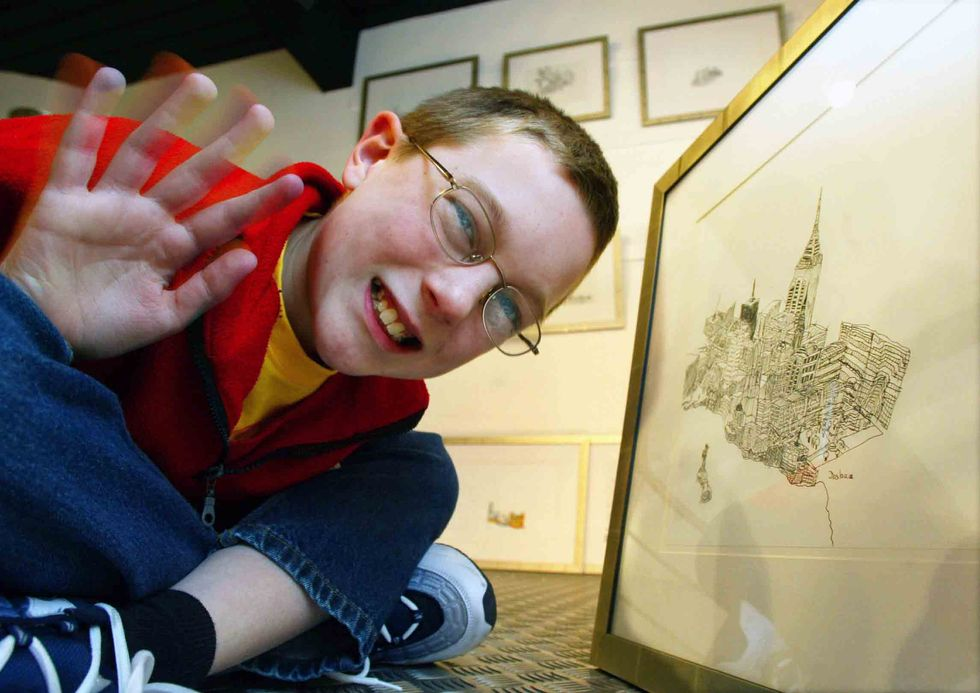 BIRMINGHAM, UNITED KINGDOM: Joshua Whitehouse (11) poses among his drawings at 'Number 9 Gallery' in Birmingham, 14 March 2002. The young artist suffering from a rare form of Autism called Aspergers syndrome have put all his artistic efforts on drawing Ne