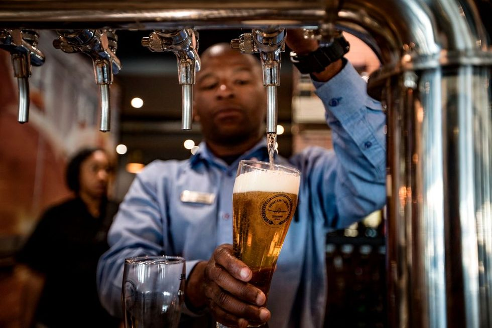 Barman Oscar Cetane (L) pours a pint at the Airport Craft Brewers, Africa's first airport brewery, at OR Tambo International Airport in Johannesburg on October 17, 2017. (Photo by Gulshan Khan/AFP/Getty Images)