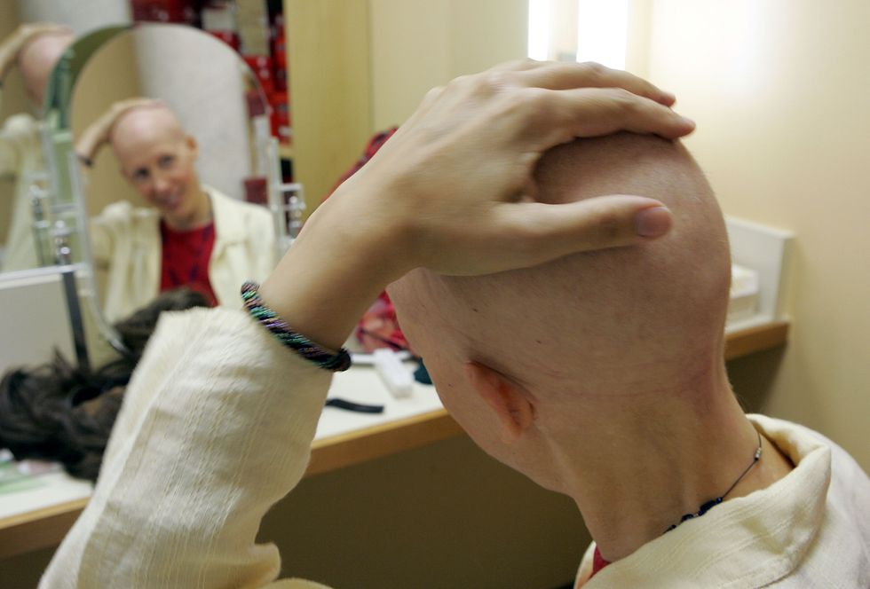 Woman with cancer looks at her head in the mirror.