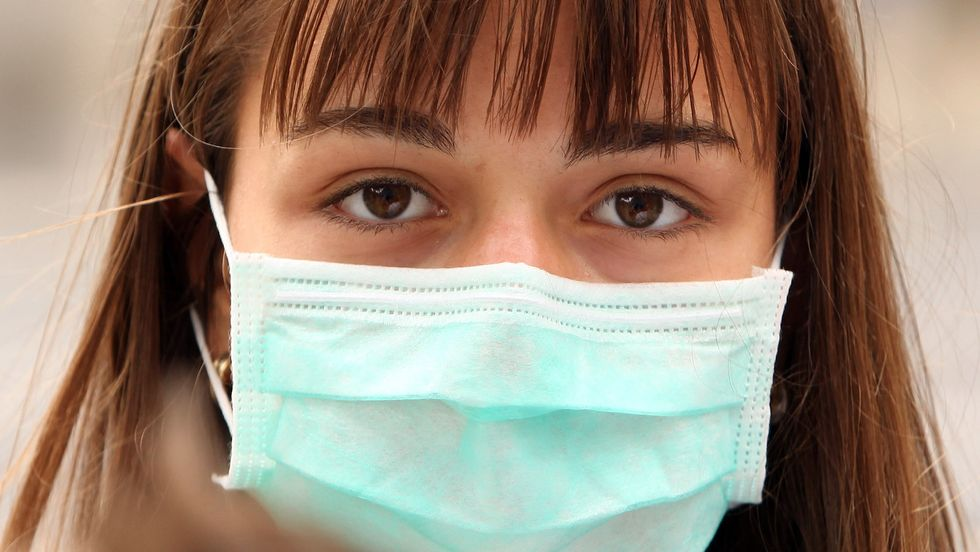 A woman wearing a surgical mask to prevent the transmission of airborne infection walks in Westminster on July 30, 2009 in London, England. (Photo by Oli Scarff/Getty Images)