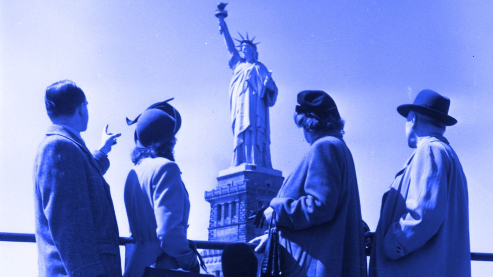 Immigrants admire the Statue of Liberty. (Getty Images)