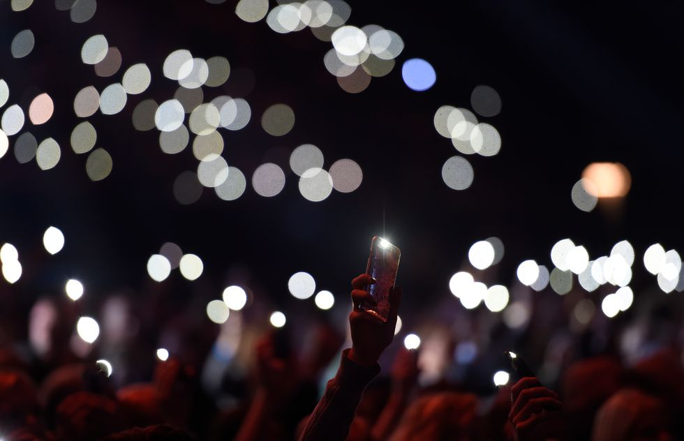 People holding up their phones at a concert. Credit: Getty Images.