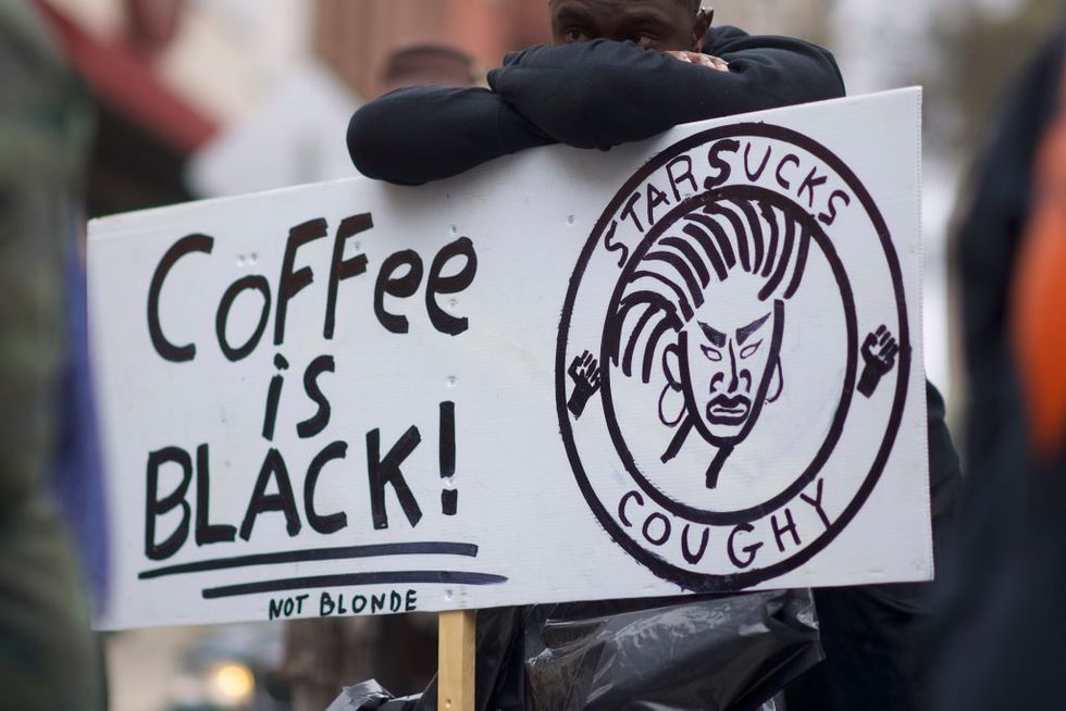 Protestor Jack Willis, 26, (C) demonstrates outside a Starbucks on April 15, 2018 in Philadelphia, Pennsylvania. Police arrested two black men who were waiting inside a Starbucks which prompted an apology from the CEO