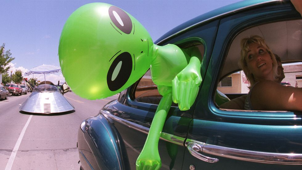 An alien doll hangs out a car window in downtown Roswell, New Mexico July 1, 2000. (Photo: Getty Images)
