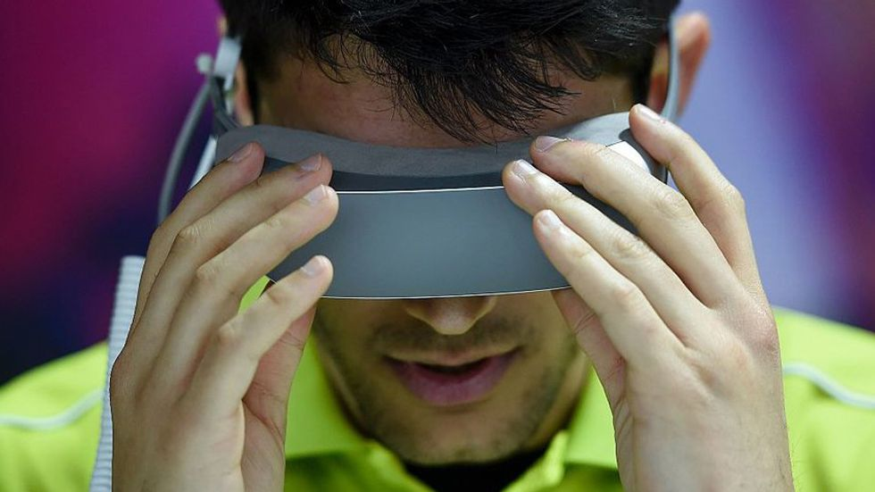 A man puts on a VR headset. (Photo: JOSEP LAGO/AFP/Getty Images)