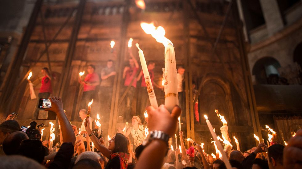 Christian Orthodox worshipers hold candles lit from a flame that emerged from the tomb believed to be of Jesus Christ. (Photo by Ilia Yefimovich/Getty Images)