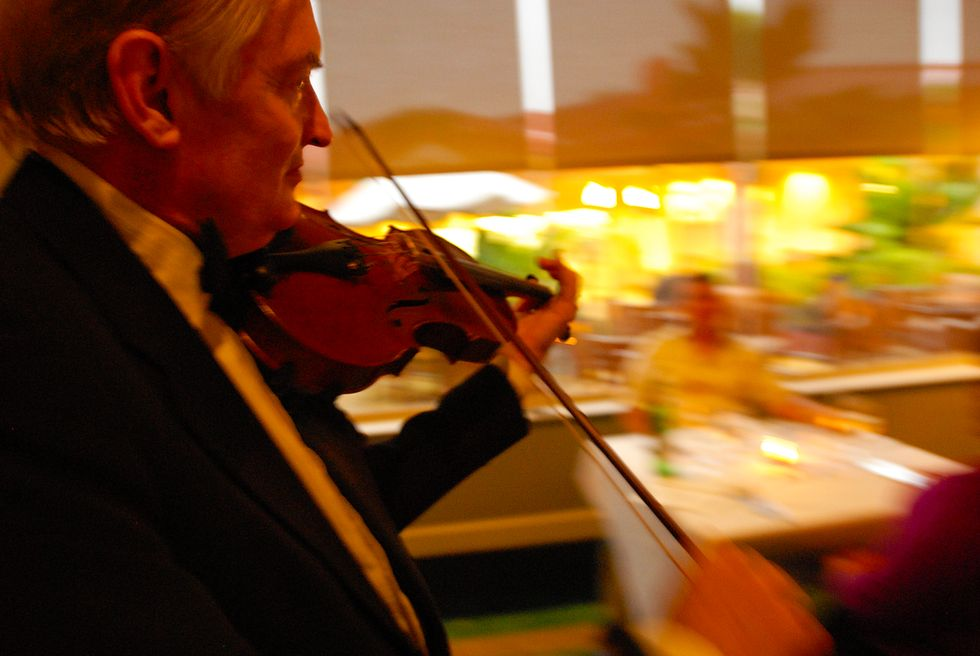 Joint Base Pearl Harbor. Hickam, Hawaii. A violinist entertains dinner guests.