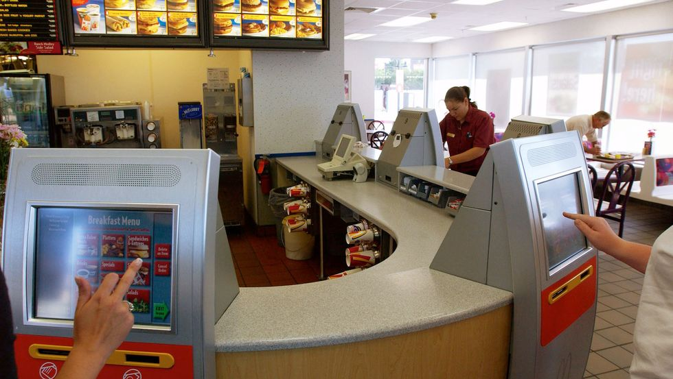 Back in 2003, customers at a McDonald's store in Denver placed orders and paid through a new kiosk system. (Photo by Kevin Moloney/Getty Images)