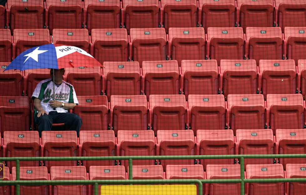 A young man sits by himself in a stadium.