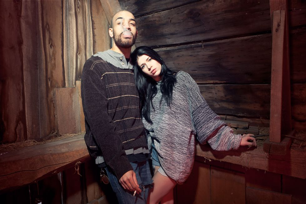 Portrait of young couple in barn while man smoking. (Thierry Lord/Getty Images)
