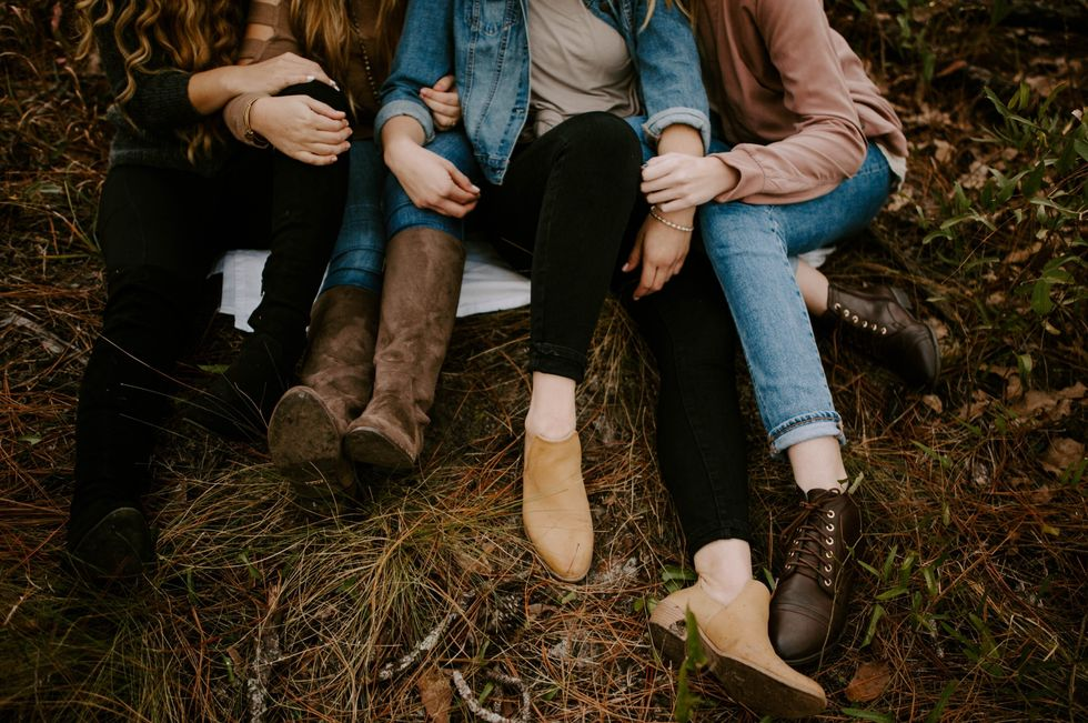3 friends sitting together in a field