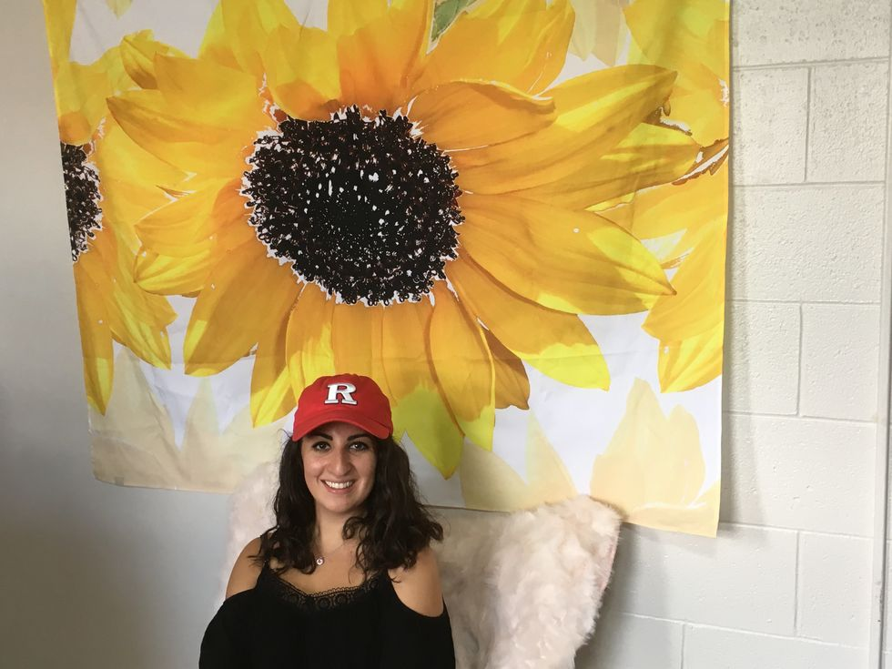 Christine sitting in her dorm room, in front of a sunflower decoration