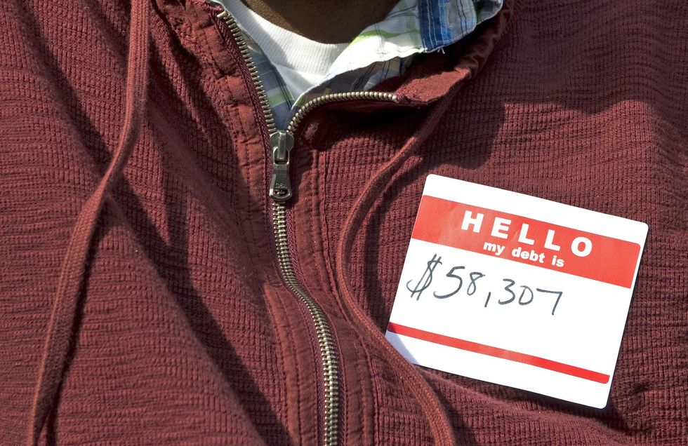"""A man with an introduction sticker on his chest that reads: """"Hello, my student debt is: $58,307"""""""