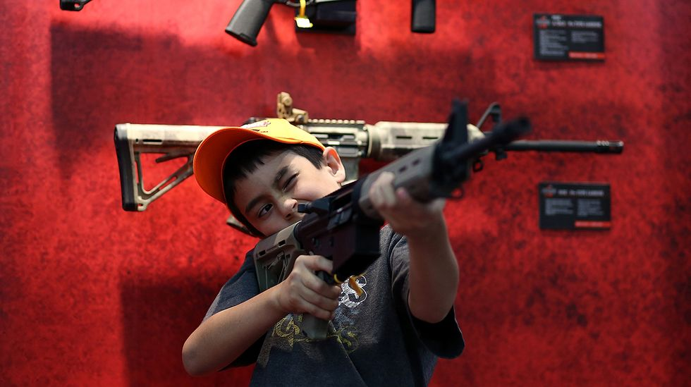 A young boy holding and aiming a gun.