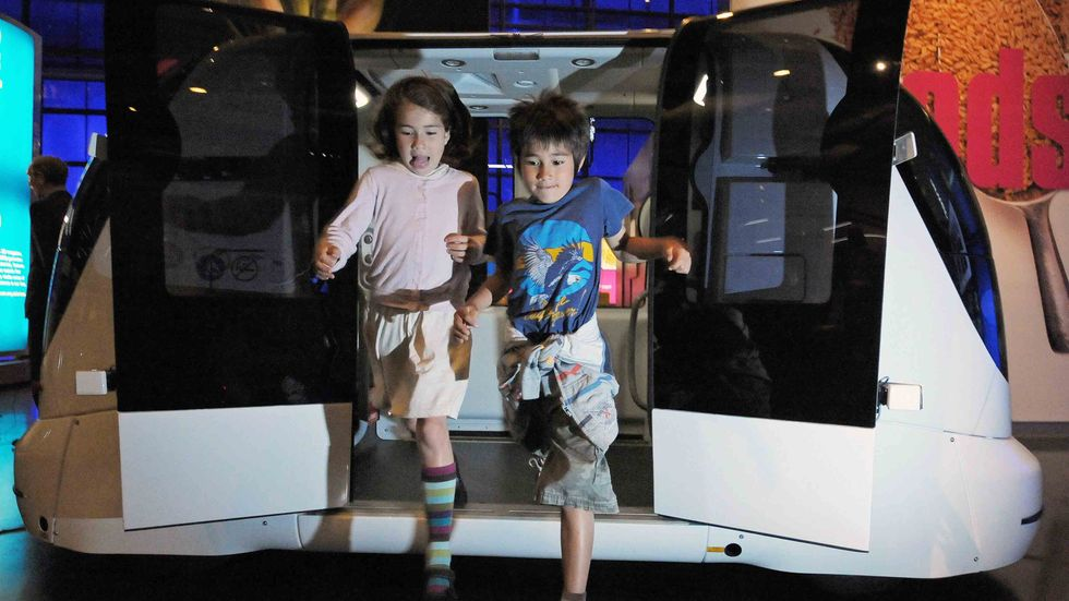 Children jump from a driverless car during a photocall at the Science Museum, in London. (CARL DE SOUZA/AFP/Getty Images)